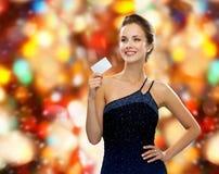拿着信用卡的晚礼服的微笑的妇女 免版税库存图片