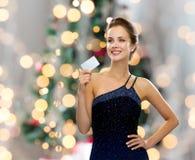 拿着信用卡的晚礼服的微笑的妇女 免版税图库摄影