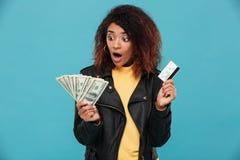 拿着信用卡的皮夹克的震惊非洲妇女 免版税库存图片
