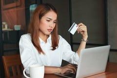 拿着信用卡的秀丽亚裔妇女在客厅 在线购物概念 图库摄影