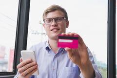 拿着信用卡&巧妙的电话的商人在办公室 人pur 库存图片