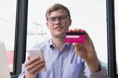 拿着信用卡&巧妙的电话的商人在办公室 人pur 免版税库存照片