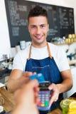 拿着信用卡读者的人在咖啡馆 图库摄影