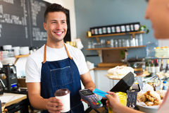 拿着信用卡读者的人在咖啡馆 库存图片