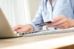 拿着信用或转账卡的手使用计算机在书桌 库存图片