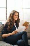 拿着信件的微笑的年轻棕色毛发的妇女 库存照片