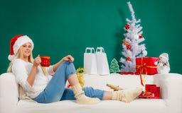 拿着假日杯子的圣诞老人帽子的妇女,喝 库存图片