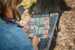 拿着假装饰金钱钞票的孩子 免版税库存照片
