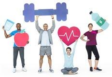 拿着健康和健身象的小组不同的人民 免版税图库摄影