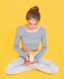 拿着健康有机快餐的莲花姿势的女孩 库存图片