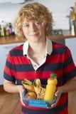 拿着健康饭盒的男孩在厨房里 图库摄影