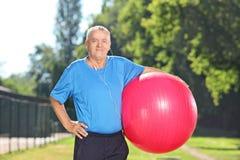 拿着健身球的成熟人在公园 免版税库存图片