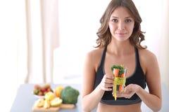 拿着充分水杯与卷尺的新鲜水果沙拉的妇女在玻璃附近 库存图片