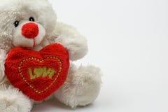 拿着充满文本爱的白色玩具熊红色心脏,隔绝在白色背景 库存照片