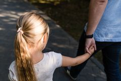 拿着充满爱的手的女儿和走在公园的爸爸 o 免版税图库摄影