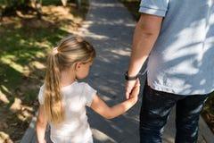 拿着充满爱的手的女儿和走在公园的爸爸 o 库存照片