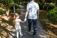 拿着充满爱的手的女儿和走在公园的爸爸 o 免版税库存照片
