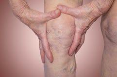 拿着充满痛苦的资深妇女膝盖 免版税图库摄影