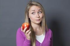 拿着充满欲望的无辜的20s女孩一个开胃苹果 库存照片