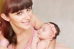 拿着充满爱她的一点逗人喜爱的sleepin的美丽的愉快的母亲 免版税库存照片