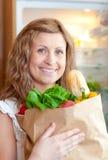 拿着光芒四射的妇女的袋子副食品 库存图片
