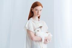 拿着兔子的严肃的红头发人妇女 库存照片