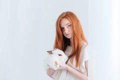 拿着兔子的可爱的红头发人妇女 免版税图库摄影