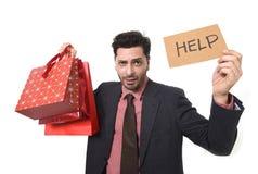 拿着全部购物袋的重音的年轻可爱的商人和看起来疲乏不耐烦的帮助标志和担心 免版税库存照片