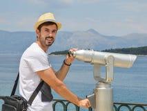 拿着公开双筒望远镜的年轻人在海边佩带的秸杆 库存照片