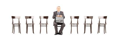 拿着公文包和等待采访的成熟商人 免版税图库摄影