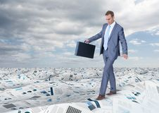 拿着公文包的商人平衡在文件海在天空下覆盖 库存图片