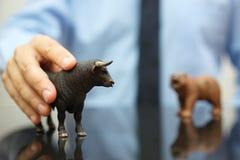 拿着公牛,看涨趋向的概念的商人在储蓄标记的 库存照片