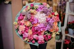 拿着兰花、玫瑰和另一朵花的美丽的花束女孩 免版税库存图片