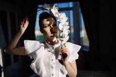 拿着兰花,坚硬阳光,时尚的美丽的白肤金发的女孩 免版税库存图片