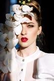拿着兰花,坚硬阳光,时尚的美丽的白肤金发的女孩 免版税库存照片