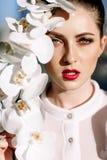 拿着兰花,坚硬阳光,时尚的美丽的白肤金发的女孩 免版税图库摄影