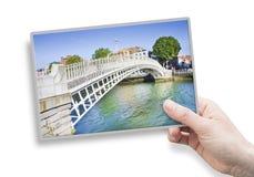 拿着关于最著名的桥梁的一只女性手一张明信片我 库存图片