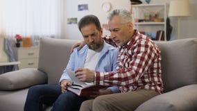 拿着册页和观看照片的沉思成年男性,召回亲戚 股票录像