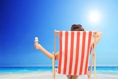 拿着冰淇凌的妇女由海洋 免版税库存图片