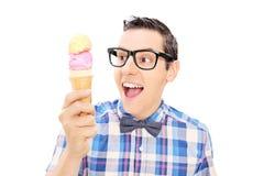 拿着冰淇凌的激动的年轻人 免版税库存照片