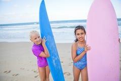 拿着冲浪板的两个愉快的女孩在海滩 免版税库存照片