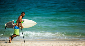 拿着冲浪板的泳装的瘸的人 免版税库存照片