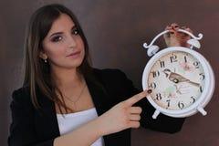 拿着减速火箭的时钟的美丽的女孩 工作室 免版税图库摄影