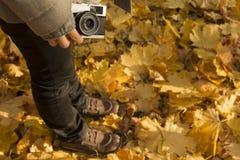 """拿着减速火箭的照相机â€的女性""""黄色在地面,秋天季节上离开 免版税库存照片"""