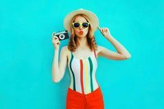 拿着减速火箭的照相机的五颜六色的年轻女人,吹的红色嘴唇送在获得夏天的草帽的空气亲吻在蓝色墙壁上的乐趣 图库摄影