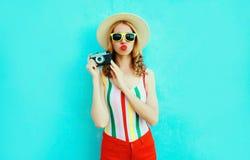 拿着减速火箭的照相机的五颜六色的年轻女人,吹的红色嘴唇送在获得夏天的草帽的空气亲吻在蓝色墙壁上的乐趣 库存图片