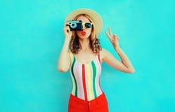 拿着减速火箭的照相机的五颜六色的年轻女人,吹的红色嘴唇送在获得夏天的草帽的空气亲吻在蓝色墙壁上的乐趣 库存照片