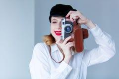 拿着减速火箭的照相机的帽子的年轻红头发人妇女 免版税图库摄影