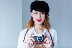 拿着减速火箭的照相机的帽子的年轻红头发人妇女 库存图片