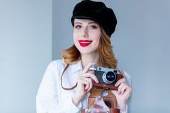 拿着减速火箭的照相机的帽子的年轻红头发人妇女 库存照片
